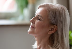 A middle age woman staying calm, closing eyes and smiling